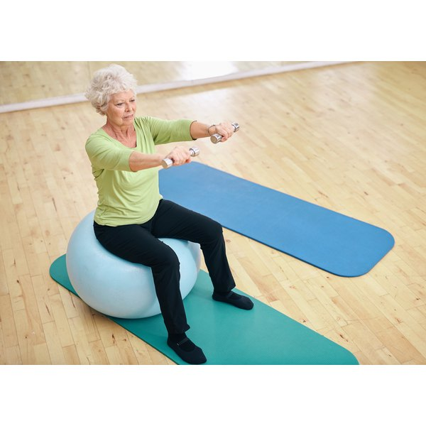 A mature woman is exercising on a stability ball in a studio.
