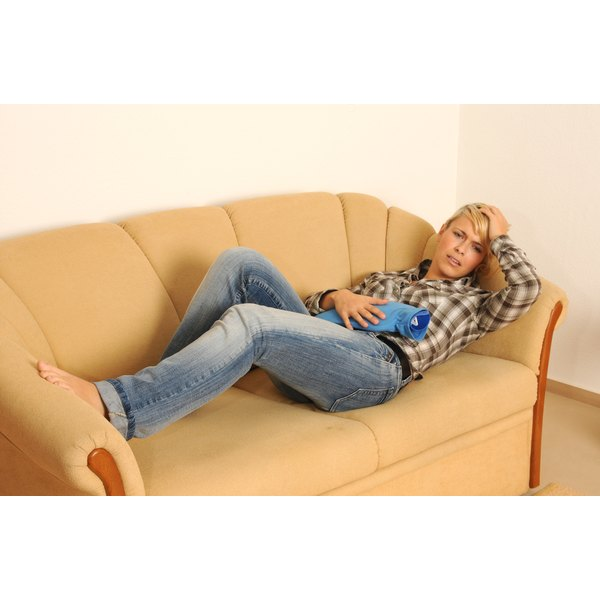 A woman with stomach pain laying on the couch.