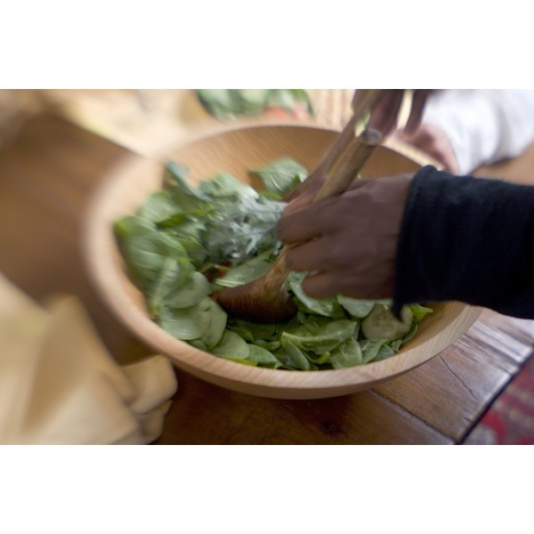 A cook prepares lettuce for a salad.