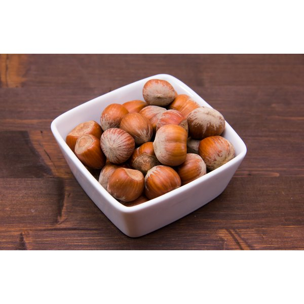 A bowl of hazelnuts on a wooden table.