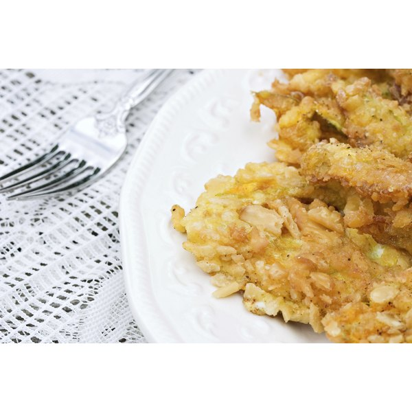 Battered pumpkin blossoms on a white plate.