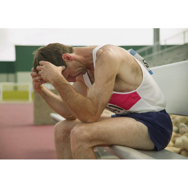 A male athlete sitting with his head in his hands.