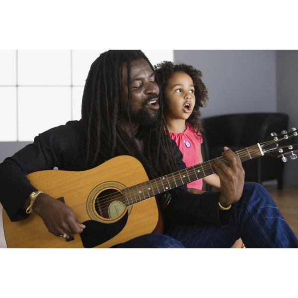 Father playing guitar and singing with his daughter