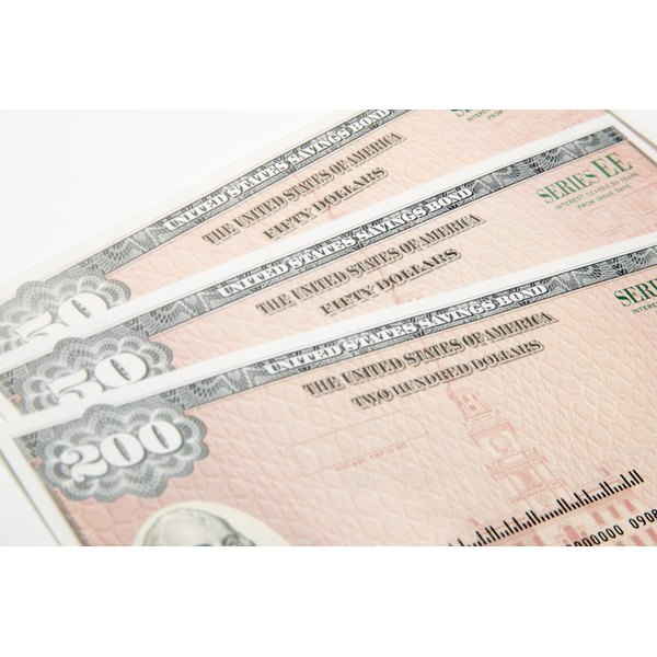 Three savings bonds sit on a white counter.