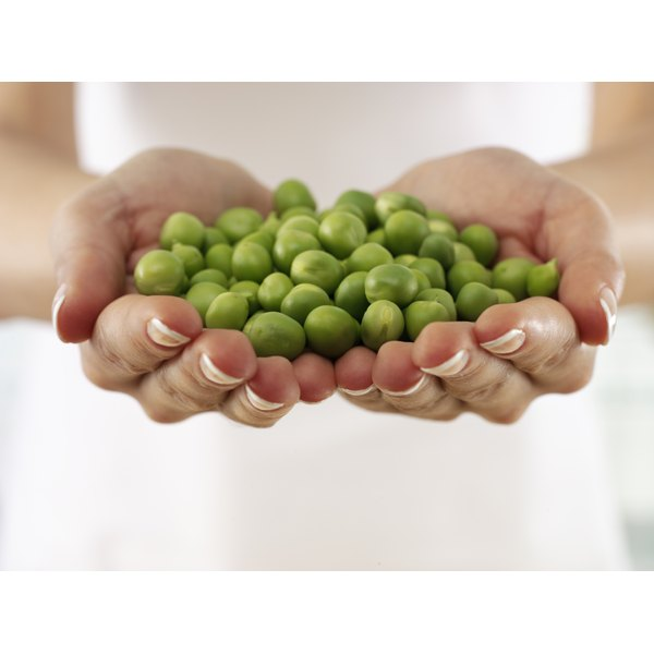 A woman is holding a handful of peas.