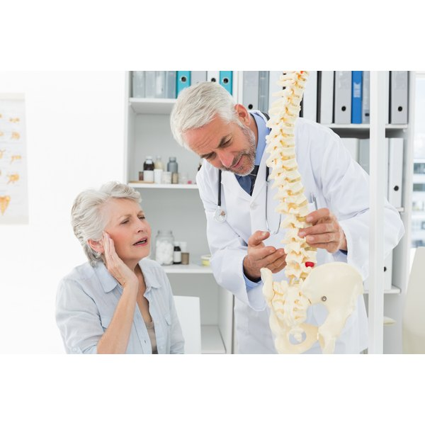 Doctor looking at a spine model with a patient