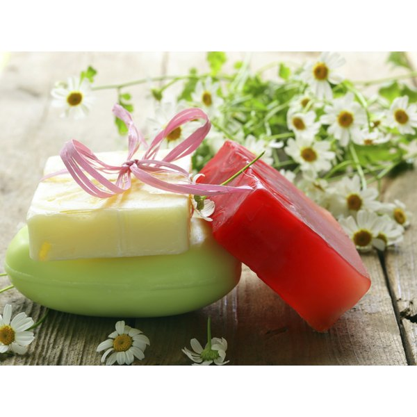 Three bars of soap on a table with fresh daisies.