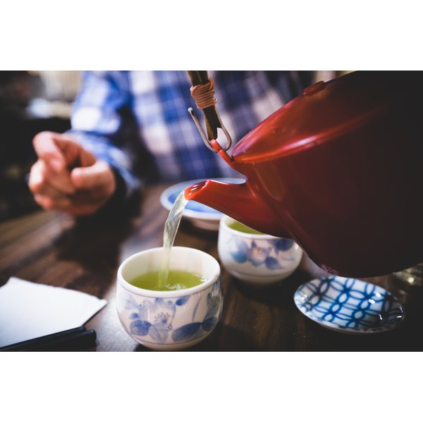 A server pours green tea at a tea house in japan.