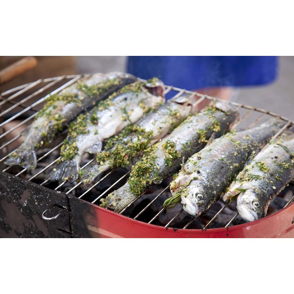 Marinated trout cooking on a barbecue.