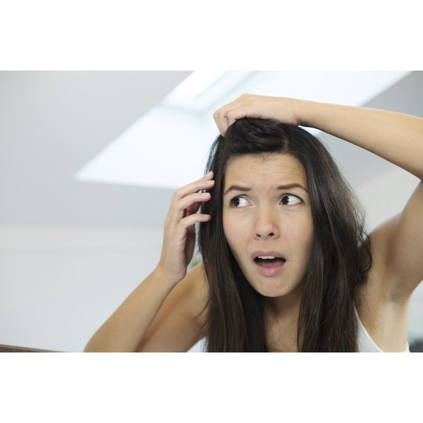 A young woman checking her hair in a mirror and looking dismayed.