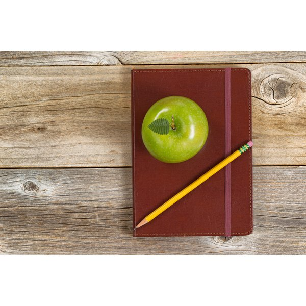 A journal, pencil and healthy snack on wood.