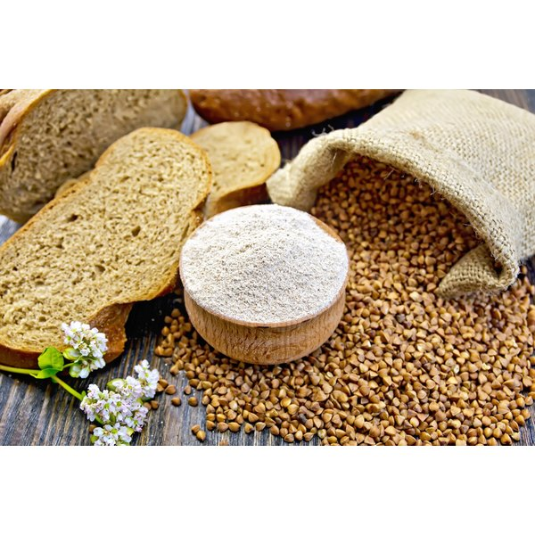 Slices of gluten-free buckwheat bread, flour and grains on a table.