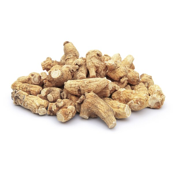 Small pieces of ginseng root stacked up on a white counter.