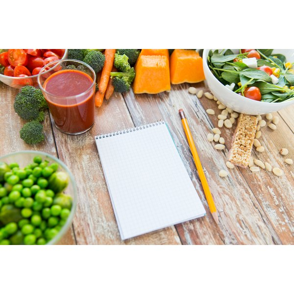 A notepad and pencil on a table with healthy foods.