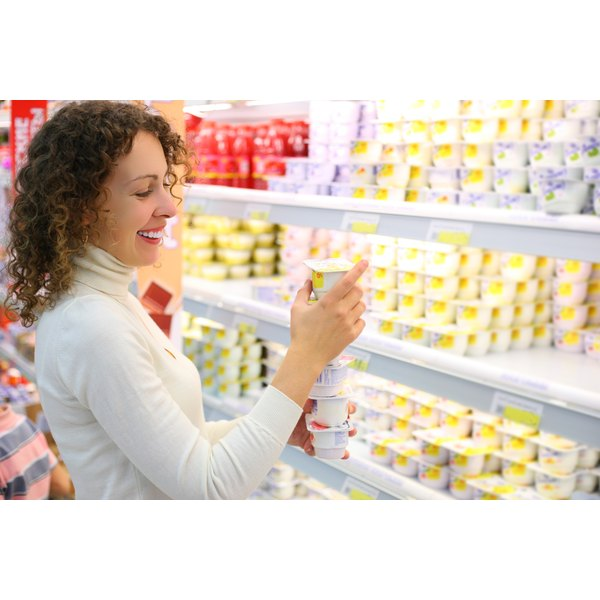 A woman is shopping for yogurt.