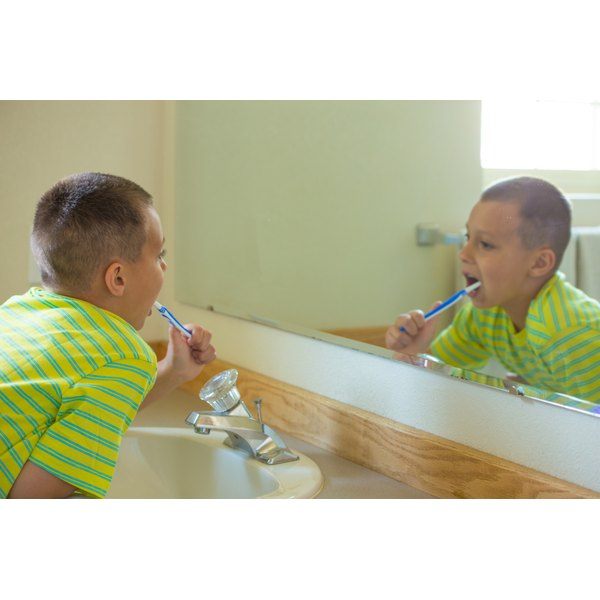 A boy wearing a clean shirt brushing his teeth in the bathroom.