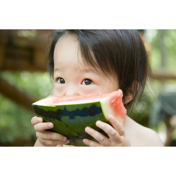 A young child is eating watermelon.