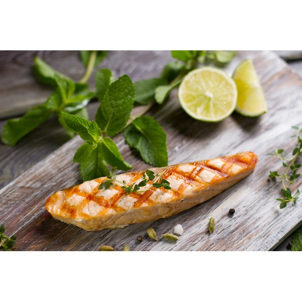 A piece of grilled salmon on a cutting board.