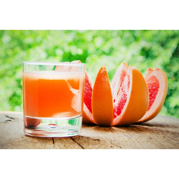 A glass of grapefruit juice sits on a table outdoors with sliced grapefruit on the side.