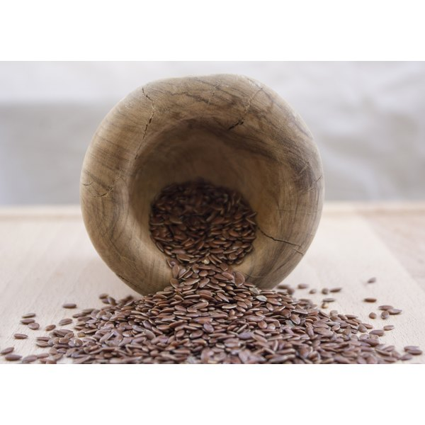 Flaxseeds spilling from a wooden bowl.