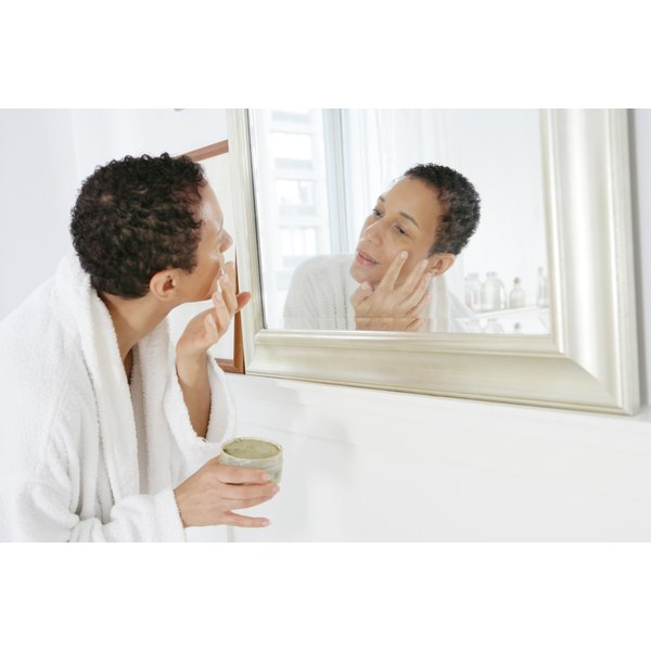 Woman looking in the mirror putting ointment on her face