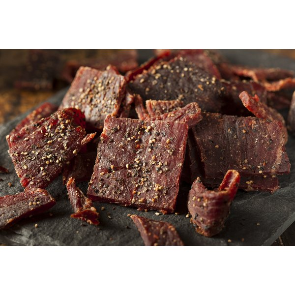 Peppered beef jerky on a cutting board.