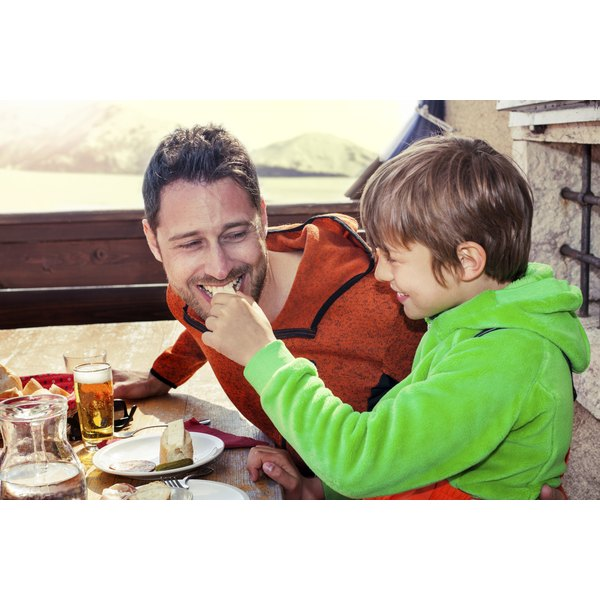 A father eats cheese from his son at a restaurant.