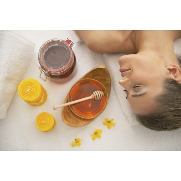 A woman laying beside a jar of honey at a spa.