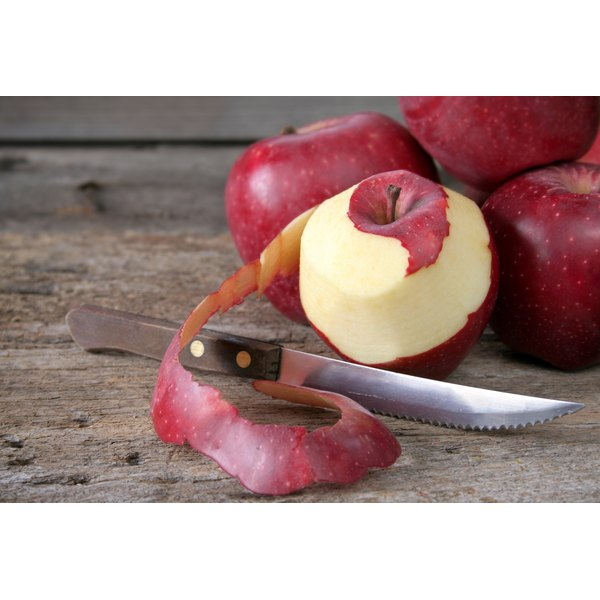 A red apple partially peeled with a knife.