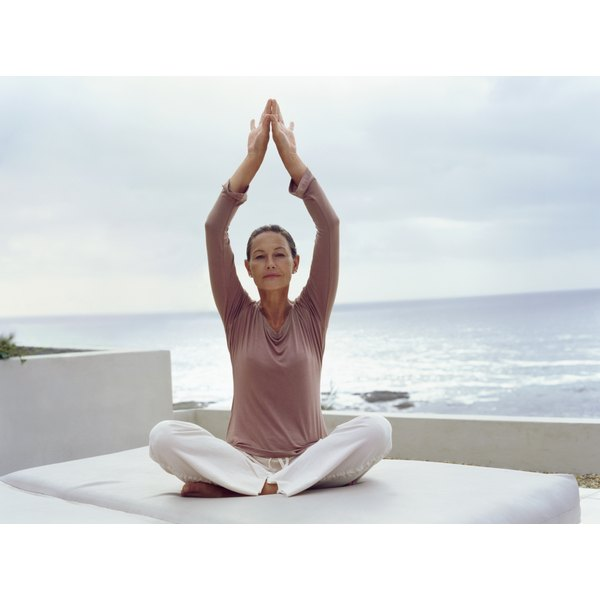 A woman relieving stress by practicing yoga in a peaceful setting.