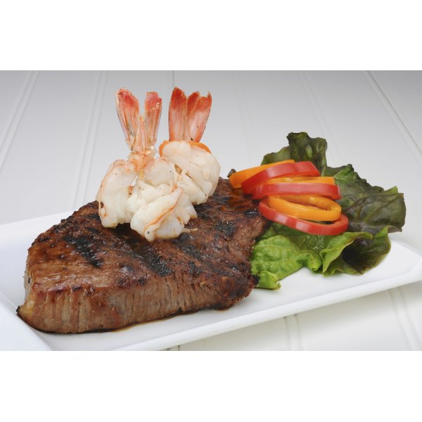 Steak and shrimp on a white plate with a side of mixed vegetables.