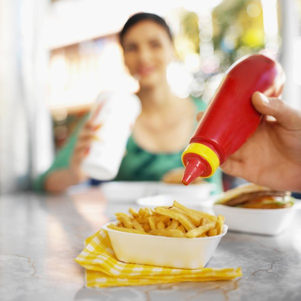 Close-up of somebody squeezing ketchup on top of fries.