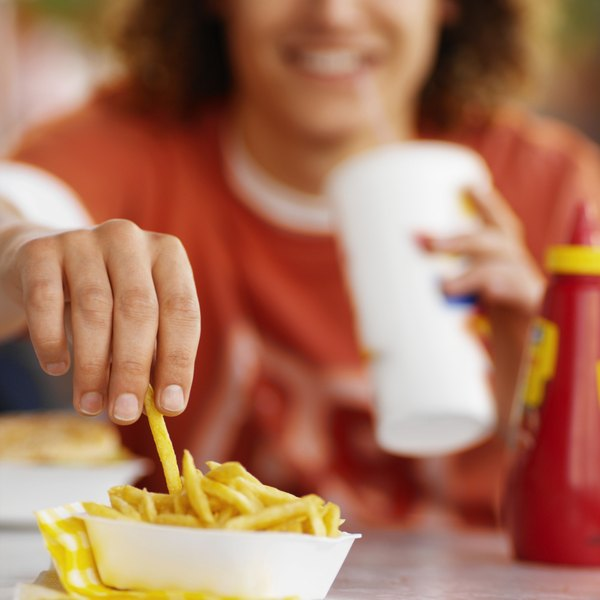 close up of man grabbing french fry out of container at fast food restaurant