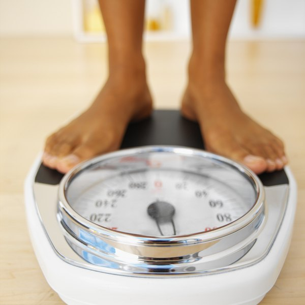 Woman's feet standing on bathroom scale