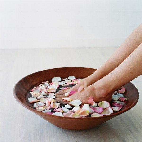 A woman with her feet in a bowl of rose water.