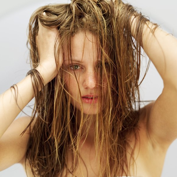 Woman with her hands in her dry hair.