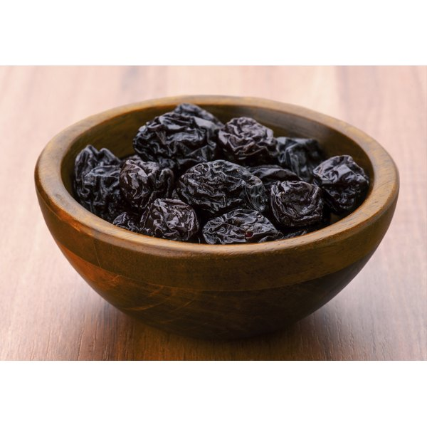 A bowl of prunes on a wooden table.