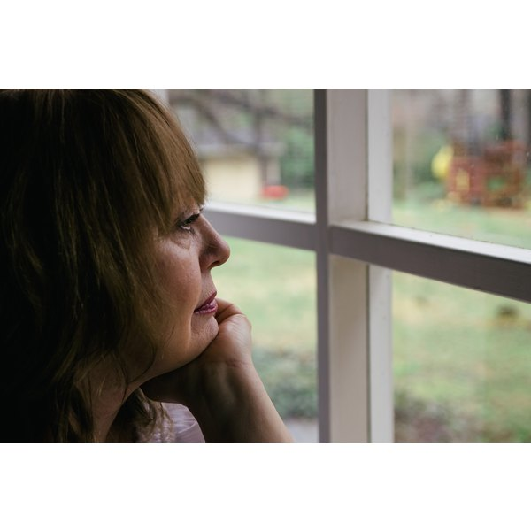 Depressed woman looking out of the window.