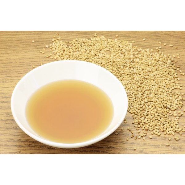 A bowl of sesame oil on a cutting board with sesame seeds.
