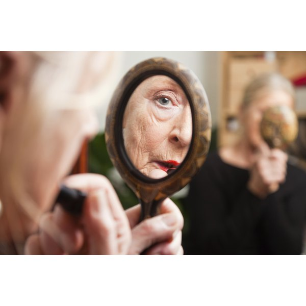 Senior woman applying lipstick in a mirror
