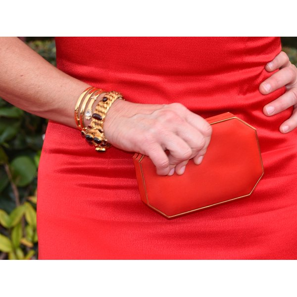 A close-up of a stylish woman in a red dress carrying a red wristlet.