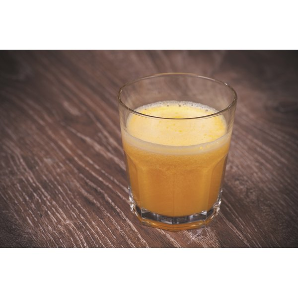 A glass of orange juice on a wooden table.