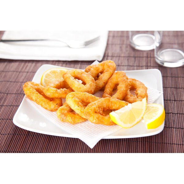 A plate of fried calamari with a lemon wedge sits on a bamboo placemat.