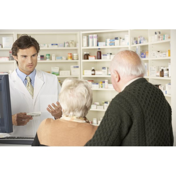 Male pharmacist serving senior couple.