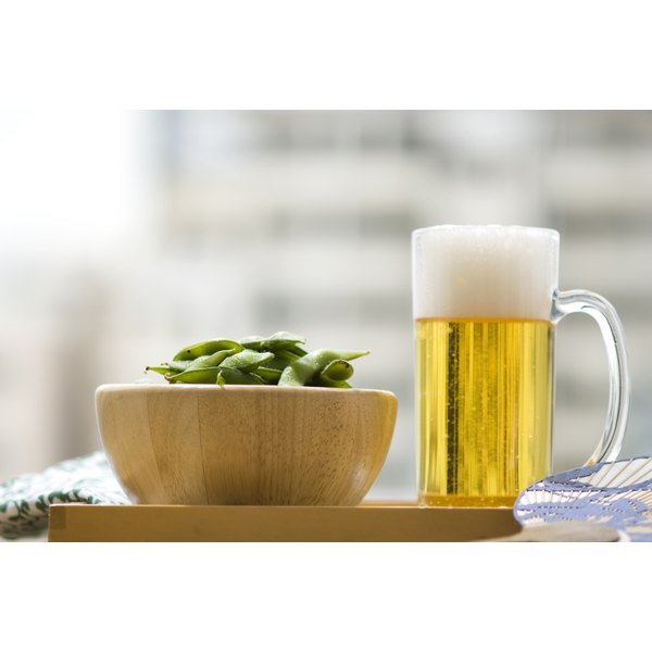 A bowl of edamame beside a pitcher of beer.
