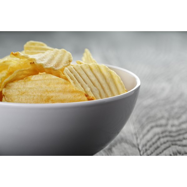 A bowl of potato chips on a wooden table.