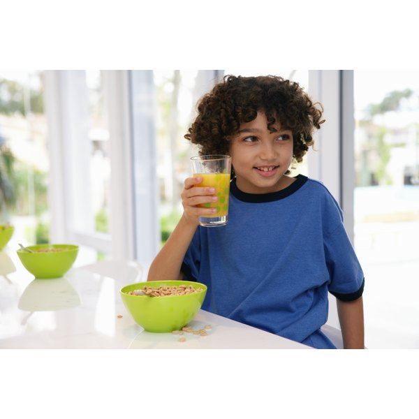 A young boy holding a glass of orange juice.