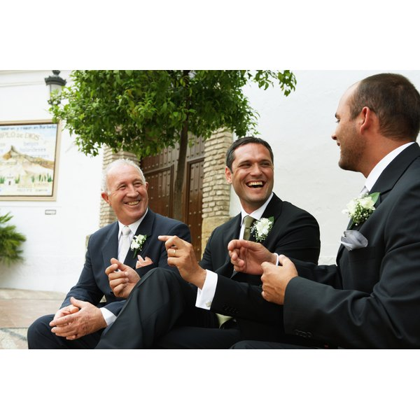The father of the groom laughing with his son and the best man after the wedding.