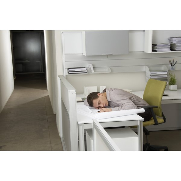 A businessman is asleep at his desk.