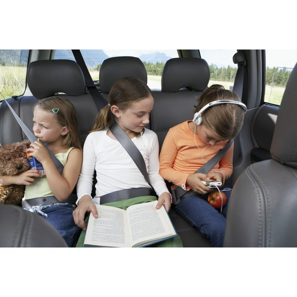 Three young girls are playing with toys in a car.